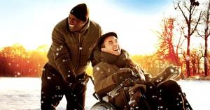 Descrição da cena do filme Intocáveis: Um homem cadeirante e seu cuidador, personagens principais do filme, se divertem em meio a uma grande área coberta por neve, com árvores desfolhadas ao fundo, iluminadas pelo sol alaranjado. Eles estão sorrindo, bem agasalhados em meio a flocos de neve espalhados no ar.