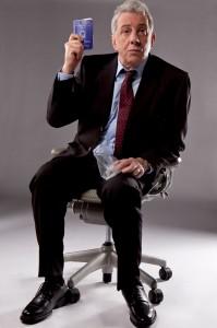 Nesta imagem o personagem do ator Marco Nanini está sentado em uma cadeira de escritório, olhando para frente. Tem a pele clara, os cabelos brancos e curtos, e aparenta 60 anos. Ele usa terno preto, camisa azul-claro e gravata vinho com bolinhas brancas. Segura um saquinho plástico na mão esquerda, que está apoiada na perna. O braço direito está dobrado para cima e a mão ao lado do corpo na altura da cabeça. Nela segura uma carteira de trabalho, azul com os escritos e o brasão da República em branco. Sua expressão é de desânimo: tem a testa franzida, as sobrancelhas levemente arqueadas, os olhos arregalados e a boca fechada e os lábios cerrados. O fundo é cinza escuro.  Crédito: Cabéra