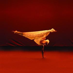 """Descrição da foto:  Imagem da coreografia """"Trama"""", na qual um bailarino apoia-se no chão com apenas um braço, deixando o corpo suspenso no ar. O tronco está voltado para cima e as penas abertas e esticadas horizontalmente. O homem tem a pele morena e corpo atlético. Usa roupa de crochê branca, composta de uma touca, camiseta cavada e saia. O fundo e o palco são vermelho escuro."""