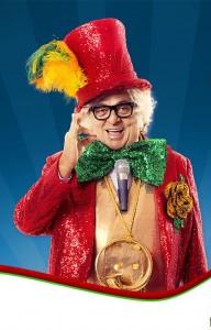 """Descrição da foto de de divulgação: o ator Stepan Nercessian é mostrado da cintura para cima, caracterizado como o """"Velho Guerreiro"""". Sorrindo expressivamente, ele tem a mão direita levantada na altura do rosto, com as pontas dos dedos polegar e indicador unidos e os outros três dedos levantados, em um gesto conhecido como """"OK"""", marca registrada de Chacrinha durante as apresentações do programa de TV. Ele veste um fraque vermelho que tem uma grande flor amarela de folhas verdes, presa do lado esquerdo do peito. Também usa um colete laranja e uma enorme gravata borboleta verde, tudo confeccionado com lantejoulas e muito brilho. Sobre os cabelos brancos, volumosos e encaracolados, uma cartola vermelha, também de lantejoulas, com plumas amarelas e verdes. Chacrinha usa óculos de grau de armação preta e grossa e tem um microfone de mão pendurado por um suporte na altura do peito, além de uma buzina dourada na altura da barriga, presa por uma corrente, também dourada e comprida, que desce do pescoço."""