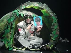 Breve descrição da imagem de divulgação - Espetáculo O Inimigo: um militar vestido com macacão cinza, capacete e óculos, está sentado de pernas cruzadas dentro de uma barraca de camping. O soldado segura uma foto de outro militar, que está de óculos e capacete. Ele aponta para a fotografia com os olhos arregalados e a boca aberta. Abaixo da fotografia, está escrito: O inimigo. A barraca é verde, com estampa camuflada e um grande furo no topo. A frente da barraca está aberta e é recoberta com algumas folhas de plástico. (Foto Fernanda Oliveira).