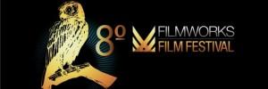 #pracegover: em um retângulo horizontal de fundo preto, do lado esquerdo da imagem, há uma coruja estilizada, em tom dourado, apoiada sobre um galho. Do lado da coruja, o número ordinal 8°, também dourado, e o nome Filmworks Film Festival, em cores branca e dourada.